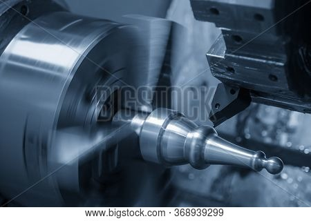 The  Cnc Lathe Machine Finish Cutting The Metal Shaft Parts. The Hi-technology Metal Working Process