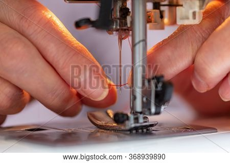 Elder Woman Fingers Inserting A Red Thread Into A Sewing Machines Needle, Close-up