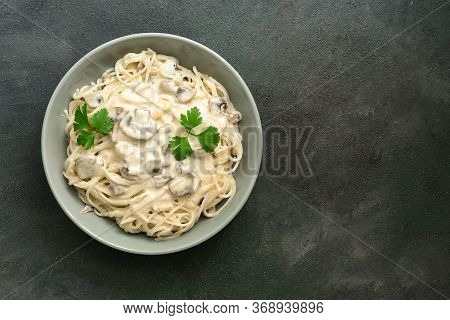 Spaghetti Pasta With Creamy Mushroom Sauce On A Dark Painted Background. Italian Traditional Dish. T