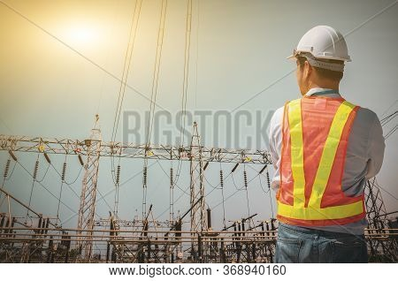 Successful Electrical Engineers Stand Against The Substation On The Blue Sky Background.