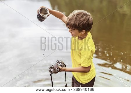 A Kid Stands In The River On Outdooor And Destroys A Mirrorless Photo Camera. The Concept Of Obsoles