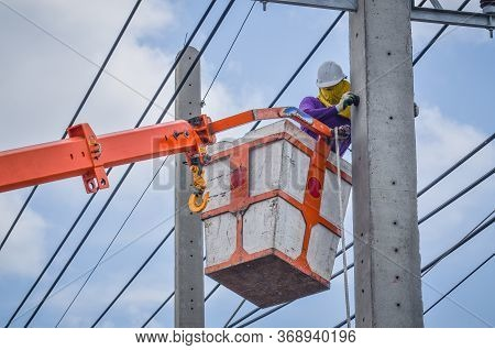 Electrician Stands On A Crane's Baskets To Install And Repair Electrical Cables.