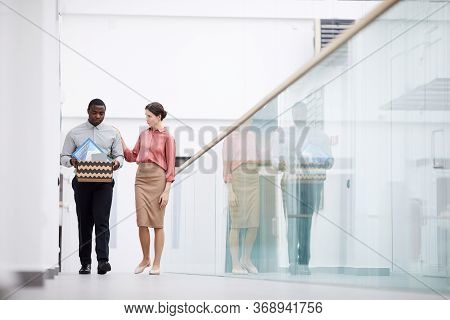 Wide Angle View At Young Female Manager Consoling African-american Colleague After Leaving Job, Copy