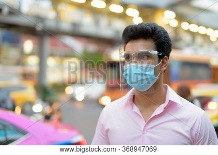 Young Indian Businessman With Mask And Face Shield Thinking In The City Streets