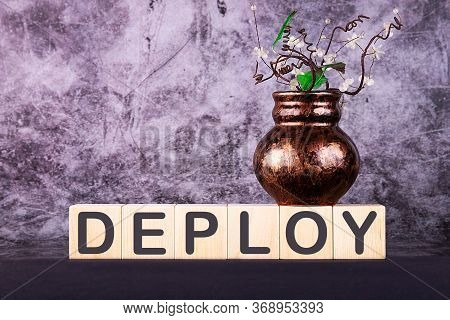 Word Deploy Made With Wood Building Blocks On A Gray Back Ground