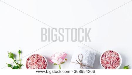 Spa Flatlay Composition. Sea Salt In Jar, Towel, Flower On White Background. Top View, Copyspace, Ba