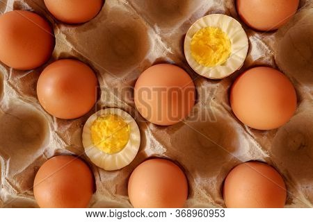 Eggs In Paper Tray. One Soft-boiled. View From Top. Boiled Halve