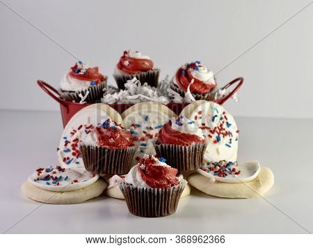 Chocolate Mini Cupcakes With Red And White Frosting And Star Sprinkles Along With Sugar Cookies With