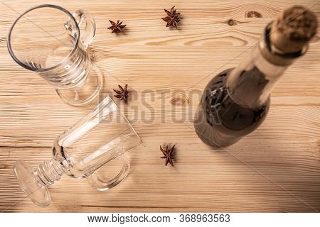 Differential Focus. Limpid Glasses On Legs For Mulled Wine, Cork Transparent Bottle With Red Wine An
