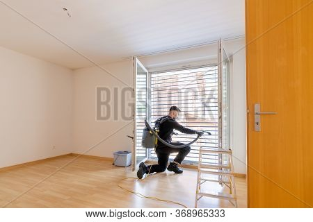 Young Male Professional Cleaner Vacuuming Dirty Window Blinds And Cleaning Htem Thoroughly