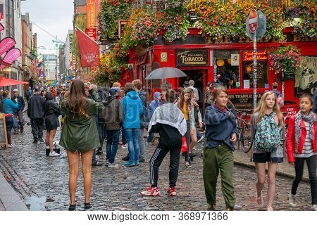 Dublin,ireland - July 30, 2019: People Walking By Famous Irish Pub , The Temple Bar