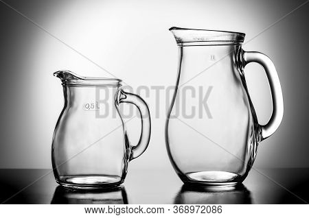 Two Empty Water Jugs Against Illuminated Background.