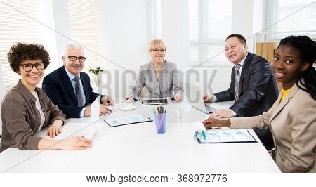 Multy-ethnic group of business people working while sitting at the office desk and smiling at camera