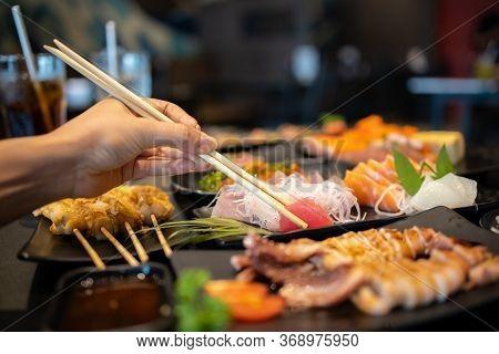 Hand Holding Tuna Sashimi Using Chopsticks, Raw Fresh Tuna Fish Sliced Served On Ice, Japanese Food