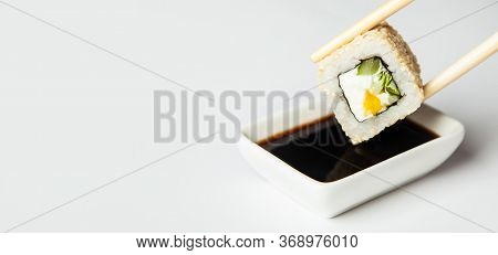 Sushi Roll In Sesame Seeds Is Held With Chopsticks And Dipped In Soy Sauce Soaked In Soy Sauce On A