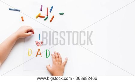 Left-handed Toddler Draws Greeting Card For Fathers Day. Kid Uses Wax Crayons To Write I Love Dad An