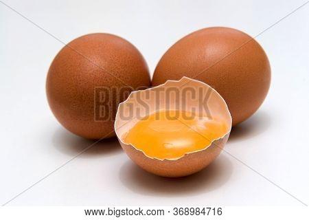 Three Eggs, One Broken Egg, Egg Yolk, Isolated On A White Background