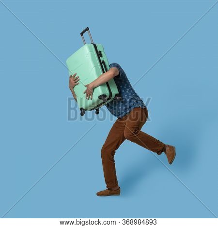 Running Man Holds Plastic Suitcase In Front Of Himself. Caucasian Traveler With Light Green Suitcase
