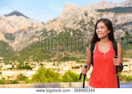 Healthy hiker woman hiking in nature mountains in Mallorca, Balearic islands, Spain. Day hike walking tour Asian girl during travel trip on spanish island visiting summer nature landscape.
