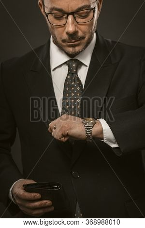 Punctual Businessman Checks Time Looking On His Wristwatch While Holding Wallet In Other Hand. Well