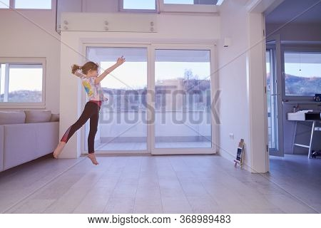 Little girl have online training over  tablet and doing modern ballet dance exercise at home. Online education concept class in modern ballet school. Social distance isolation in coronavirus