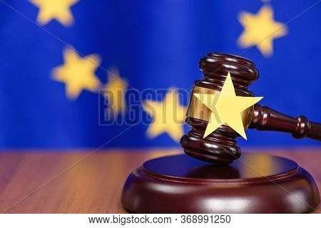 Judicial Justice And Law. Eu And Court. Judges Gavel On The Table And The Eu Flag In The Background.