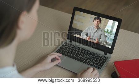 Woman Having Video Chat With Colleague At Table In Office, Closeup