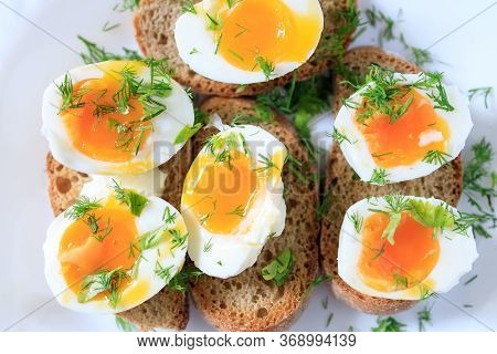 Soft-boiled Egg Halves With Dill On Whole Grain Toast Bread On A White Plate. Close-up, Top View. He