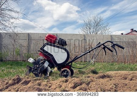 Garden Tiller To Work, Tractor Cultivating Field At Spring, Loosens Soil By Petrol Cultivator