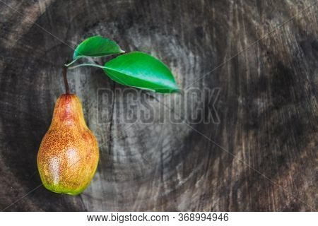 One Juicy Ripe Pear With Leaves Lies On A Wooden Vintage Dark Background. Top View, Copy Space.