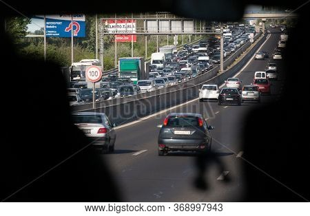 Traffic Jam, View From Car Window. Dense Stream Of Cars Moving Towards Both Sides. View Through Wind