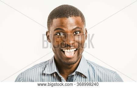Funny African American Man Toothy Smiles Showing Tongue While Looking At Camera. Young Male Entrepre