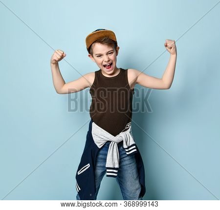Atractive Boy In Cap, Undershirt, Jeans And Hoodie Tied Around His Waist. He Clenched His Fists Show