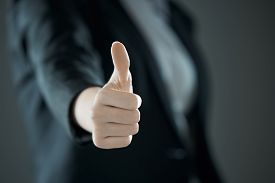Thumbs Up From Girl. Business Concept Of Success Against The Background Of Suit In Blur.