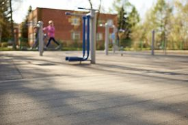 Blurred Background Of A Street Sports Field With Exercise Equipment. Someone Is Working Out On A Str