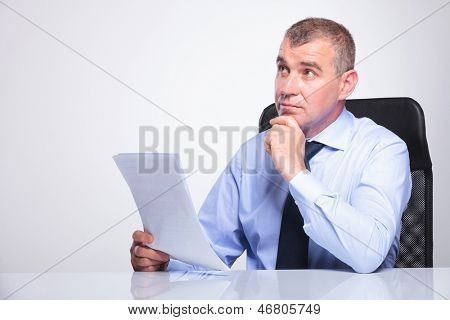 senior business man sitting pensive at his desk with some documents in his hands, looking away from the camera. on gray background