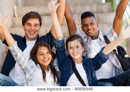 excited high school students with arms outstretched outdoors