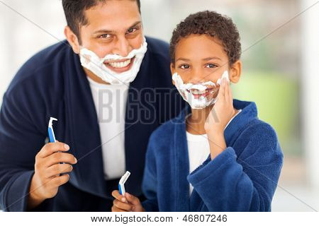 happy son playing with father's shaving foam at home
