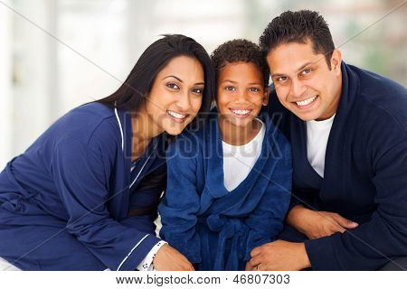 cute young indian family in their nightclothes sitting on bed