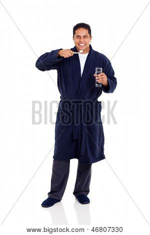 smiling indian man wearing pajamas brushing teeth isolated on white background