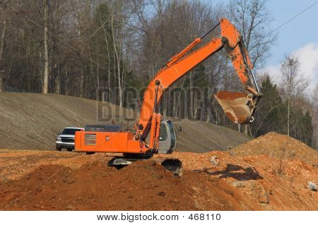 bright colored trackhoe moving dirt for new highway poster