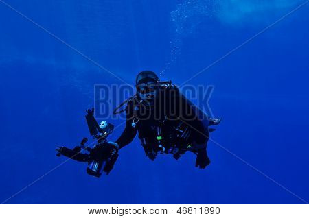 Underwater photographer with big camera and flashes
