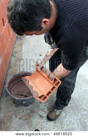 Mason applying cement on a cinderblock