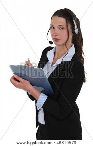 Brunette call-center worker writing on clip-board