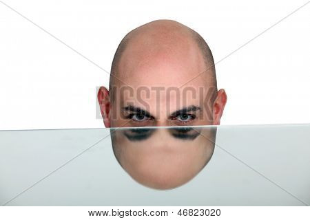 Bald man's head mirrored in a table