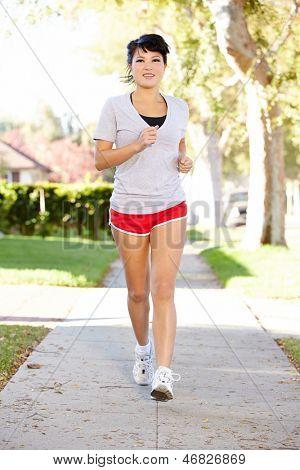 Female Runner Exercising On Suburban Street