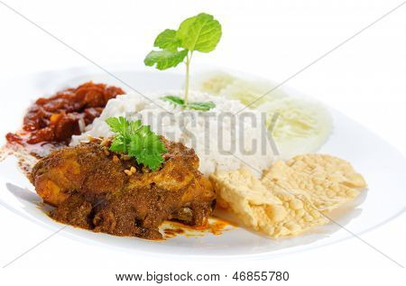 Nasi lemak is traditional malaysia spicy rice dish. Served with belacan, ikan bilis, acar, peanuts and cucumber. Isolated on white background, popular malaysian food. Asian cuisine.