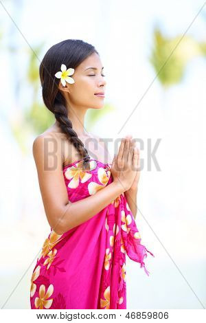 Meditating spiritual woman in meditation on beach vacation. Natural serene beauty relaxing in zen moment wearing pink sarong and flower during summer holidays travel on Big Island, Hawaii, USA.