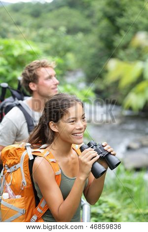 Hiking couple of hikers in outdoor activity wearing backpacks. Woman hiker looking with binoculars smiling happy. Healthy lifestyle image from Iao Valley State Park, Wailuku, Maui, Hawaii, USA.
