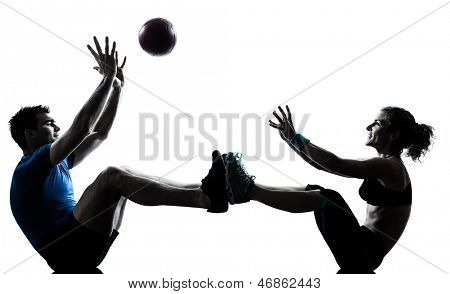 one caucasian couple man woman personal trainer coach exercising tossing fitness ball silhouette studio isolated on white background